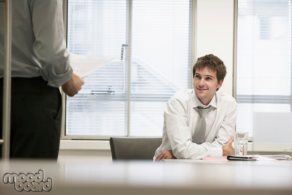 Smiling businessmen sitting in office listening to other businessman