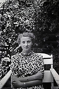 young adult woman posing in chair with garden hedge background 1950s Netherlands