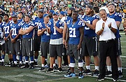 Members of the Indianapolis Colts including Indianapolis Colts head coach Chuck Pagano (white shirt) clap in support of the announcement canceling the game before the 2016 NFL Pro Football Hall of Fame preseason football game against the Green Bay Packers on Sunday, Aug. 7, 2016 in Canton, Ohio. The game was canceled for player safety reasons due to the condition of the paint on the turf field. (©Paul Anthony Spinelli)