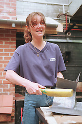 Young woman learning plumbing skills shaping lead flashing,