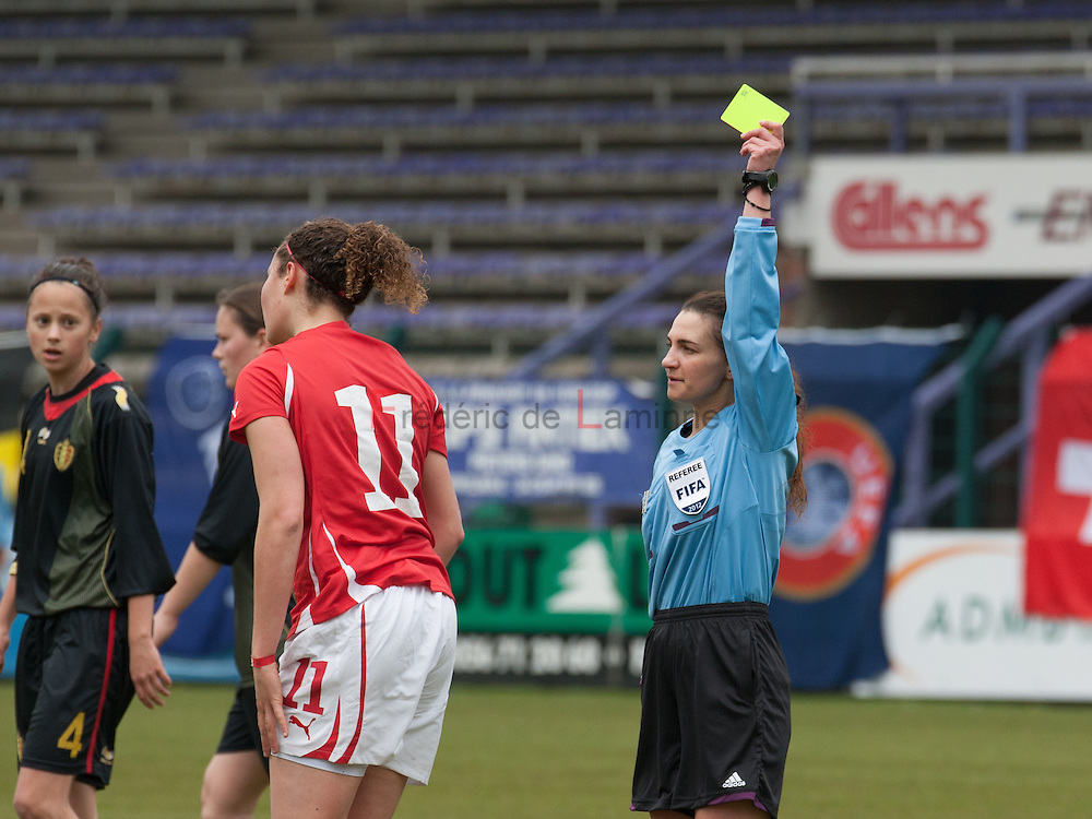 21120413 - HARELBEKE, BELGIUM : Referee Konstantina Mpoumpouri (GRE) gives a yellow to Switzerland's  Sabrina Ribeaud (11)  during the Second qualifying round of U17 Women Championship between Switzerland and Belgium on Friday April 13th, 2012 in Harelbeke, Belgium.