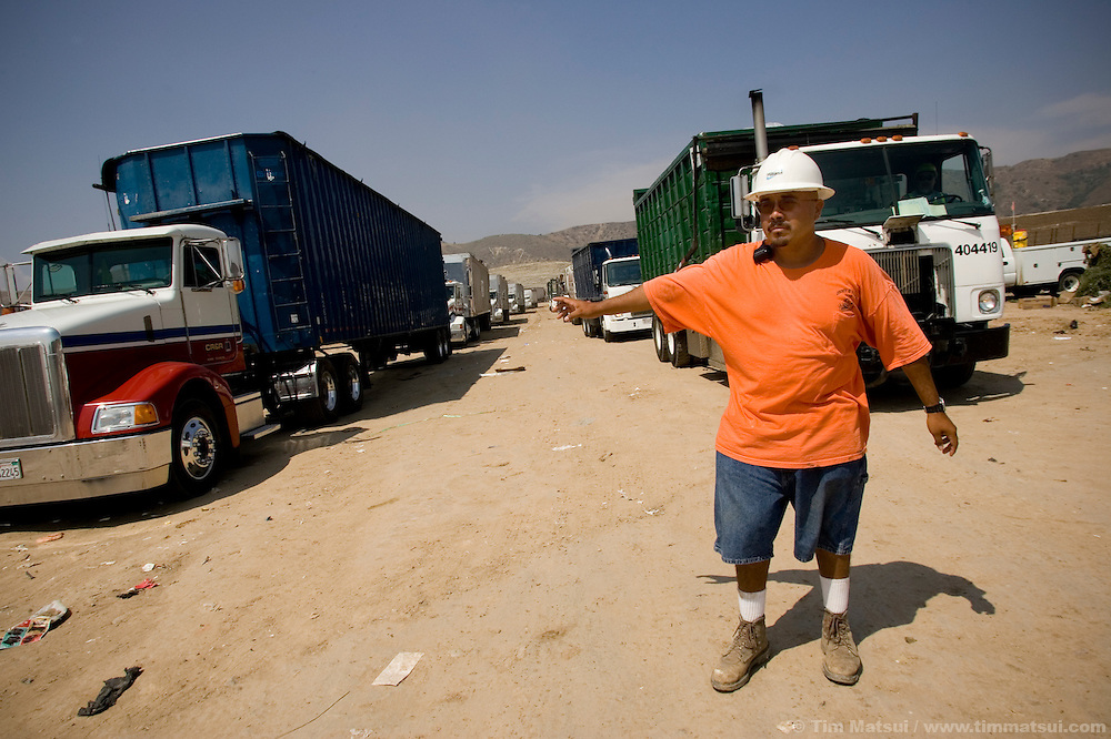 TUESDAY JULY 25, 2006 - LOS ANGELES, CALIF.  Albert Hernandez directs garbage trucks lined up to dump their loads at the Frank R. Bowerman Landfill near Los Angeles in Orange County, Calif. Seattle-based Prometheus is installing a facility to liquify the methane gas the landfill produces and currently flares into the atmosphere.