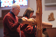 Catholics venerate the cross during a Good Friday service at St. Patrick Church in Menasha, Wis. April 10. (Photo by Sam Lucero)