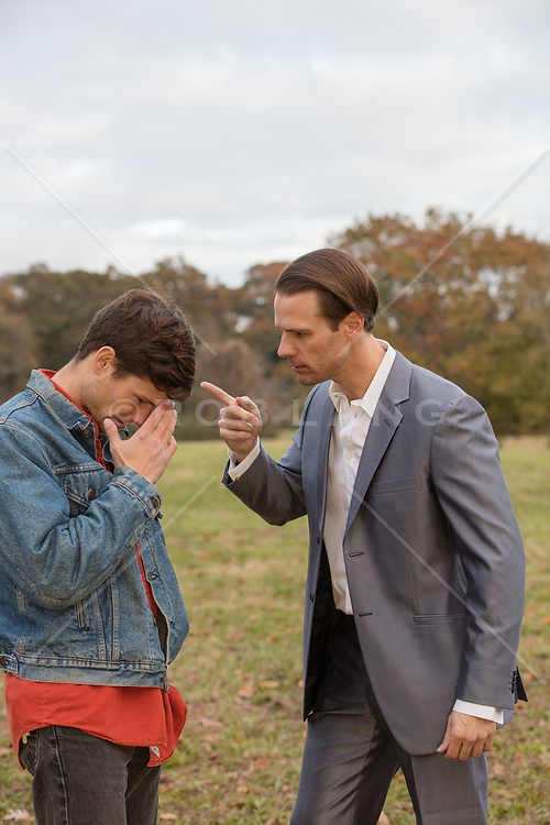 older man in a suit scolding a younger man in jeans jacket