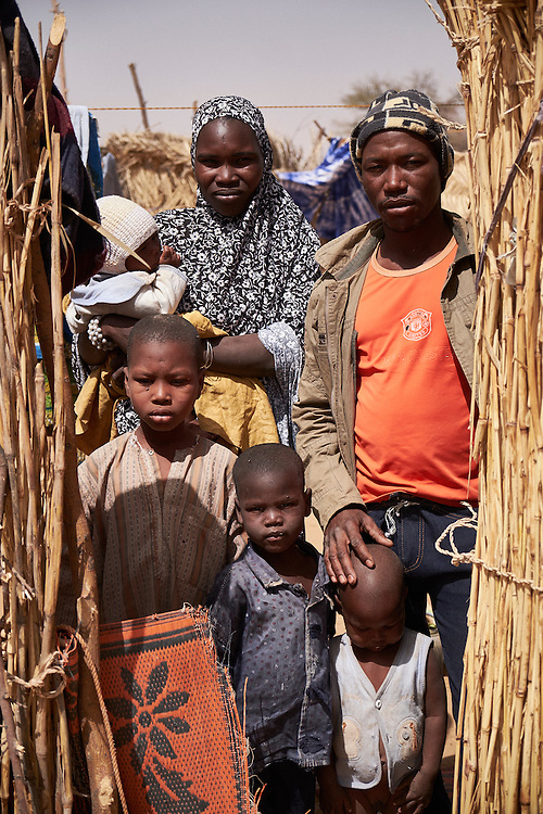 Abdou Malamdjibril with his wife Falmata and children in the village of Guidan Kaji near the border with Nigeria on the outskirts of Diffa, Niger on February 13, 2016. hey traveled to the village from Nigeria  and were displaced 5 times in the last year, crossing 2 countries. Abdou attempts to pick up labouring work in a nearby village when available. They received blankets and clothes from Caritas during the last distribution. Displaced people from Niger and Nigeria are sheltering in the village after fleeing at the nearby border. Many of the families had witnessed attacks by Boko Haram in their villages or had fled because of other villages around them being attacked. Caritas undertook a distribution of sleeping covers, mosquito nets, pots and money transfers.
