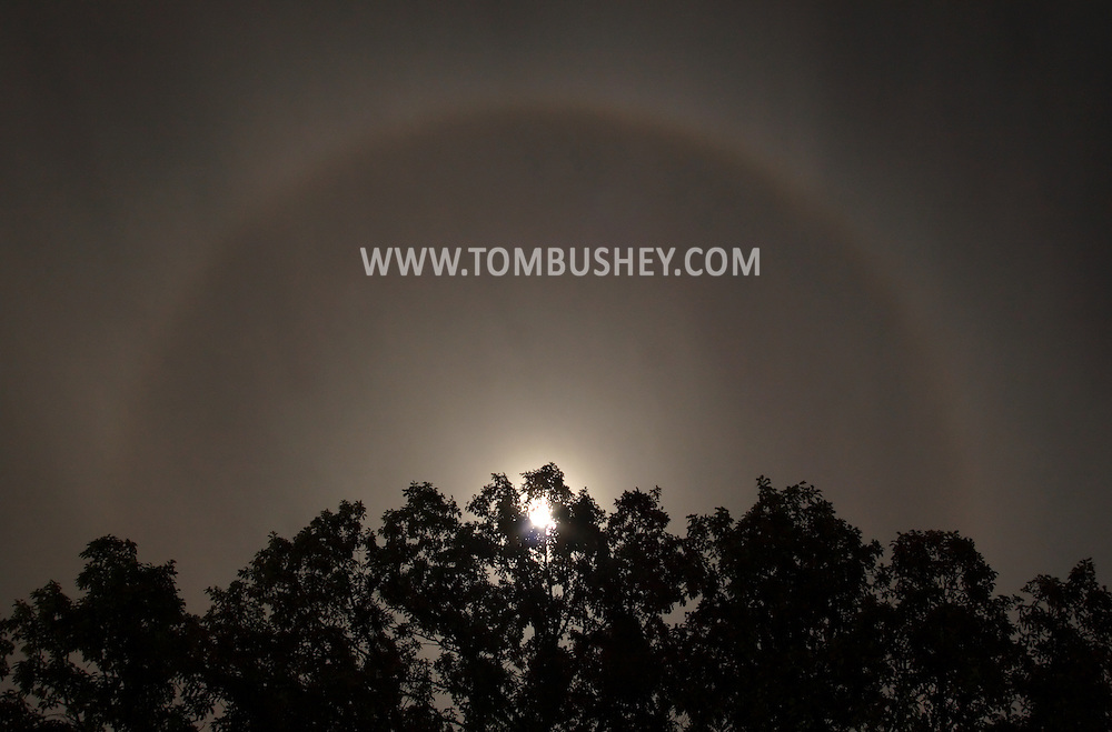Middletown, NY - A ring forms around the moon on the night of Oct. 13, 2008. The ring around the Moon is caused by the refraction of moonlight through ice crystals suspended in the upper atmosphere. A moon ring or moon halo will always be roughly the same size - 22-degrees across the sky - because the crystals bend the light at a 22-degree angle from their original path. The moon itself is overexposed in this 4-second frame.