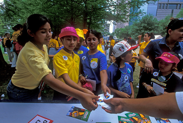 Stock photo of a group of children receiving stickers at a booth at the International Festival in downtown Houston Texas