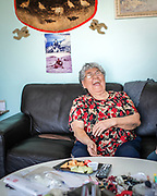 Annie Gordon laughs inside her home in Aklavik. Her and Danny sell handcrafts, pelts, and clothing out of their home.