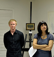 Port Washington, New York, U.S 6th October 2013.  MATTHEW WEIGLE, Juror of Awards, and SHELLEY HOLTZMAN, President of the Art Guild of Port Washington (TAG), are next to Wigle's oil painting displayed on an easel at The Artists Reception for Members Showcase of the, at The Graphic Eye Gallery.