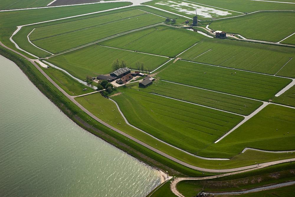 Nederland, Noord-Holland, Gemeente Zeevang, 28-04-2010; Polder de OosterKoog, buitendijks land van de Zuiderzee, in de voorgrond. Op het tweede plan Polder de Etersheimerbraak. Deze laatste  polder is een voormalige 'braak' (dijkdoorbraak) die in 1632 bedijkt is (en vervolgens drooggemaakt). Tijdens de watersnood van 1916 stond het water aan de kruin van de Zeevangszeedijk (Zuiderzee- of IJsselmeerdijk). Om de dijk op te hogen - met klei, zijn in 1917 in de Etersheimerbraakpolder kleiputten gegraven (het gedeelte rechts van de boerderij). .Foreground polder outside the seawall, behind it the Polder Etersheimerbraak. This polder is a former 'breach' (levee failure) that was diked in 1632 (and subsequently dried). During the flood of 1916, the water stood at the top of the Zeevang seawall. To raise the top of the seawall, clay was needed and in 1917 clay pits were dug in the Etersheimerbraakpolder (the part to the right of the farm)..luchtfoto (toeslag), aerial photo (additional fee required).foto/photo Siebe Swart