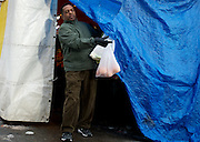 February 12, 2011 - A man pushes a protective tarp out of the way as he exits a vendor stand at Haymarket in Boston, MA. Photo by Lathan Goumas.