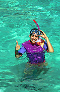 Woman gives the thumbs up to indicate good snorkeling conditions, Belize Ambergris Caye..