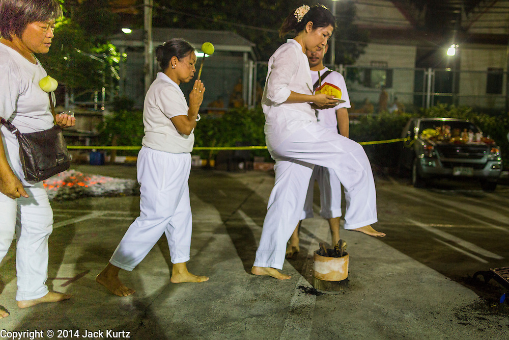 01 OCTOBER 2014 - BANGKOK, THAILAND: A woman jumps over a small fire pit during a firewalk at Wat Yannawa (also spelled Yan Nawa) during the Vegetarian Festival in Bangkok. The Vegetarian Festival is celebrated throughout Thailand. It is the Thai version of the The Nine Emperor Gods Festival, a nine-day Taoist celebration beginning on the eve of 9th lunar month of the Chinese calendar. During a period of nine days, those who are participating in the festival dress all in white and abstain from eating meat, poultry, seafood, and dairy products. Vendors and proprietors of restaurants indicate that vegetarian food is for sale by putting a yellow flag out with Thai characters for meatless written on it in red.     PHOTO BY JACK KURTZ
