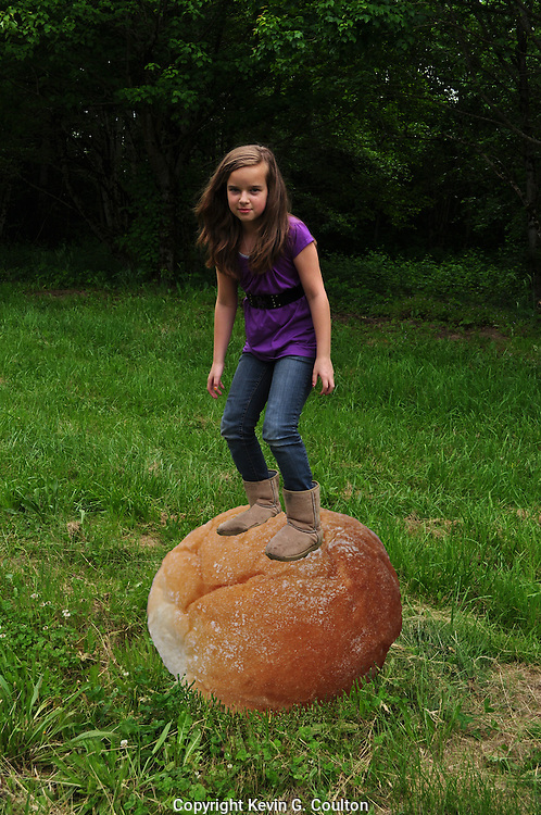 "Humorous photograph of a girl standing on an oversized dinner roll visually depicting the saying ""You're on a roll!"""