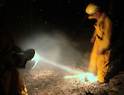 Fire fighter Ken VanStronsen from Allouez, MI breaks up a potentially dangerous stump hole while working the night shift on the Sleeper Lake forest fire north of Newberry in the upper peninsula.  The fire has been burning an average of 5,000 acres a day.