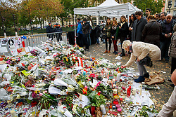 © Licensed to London News Pictures. 16/11/2015. Paris, France. Mourners visit a memorial outside Bataclan Cafe in Paris, France following the Paris terror attacks on Monday, 16 November 2015. Photo credit: Tolga Akmen/LNP