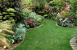 Small town garden with well kept lawn, brick edging and curving borders
