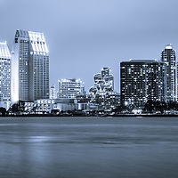 Photo of San Diego at night with downtown San Diego buildings along San Diego Bay. Image is high resolution, toned blue, and was taken in 2012.