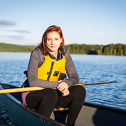 A young woman in a canoe on Long Pond in Maine's north woods. Near Greenville, Maine.