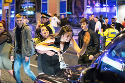 """© Licensed to London News Pictures . 17/12/2016 . Manchester , UK . A woman pulls another woman away , as the second woman strikes the bonnet of a cab with her hand . Revellers out in Manchester City Centre overnight during """" Mad Friday """" , named for being one of the busiest nights of the year for the emergency services in the UK . Photo credit : Joel Goodman/LNP"""
