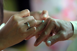A bride puts on a wedding ring to her groom during a Valentine s Day mass wedding in Quezon City, the Philippines, Feb. 14, 2013. About 4000 couples around the Philippines were married in celebration of Valentine s Day, February 14, 2013. Photo by Imago / i-Images...UK ONLY