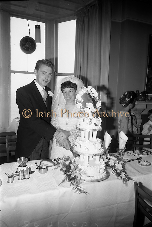 """16/09/1967<br /> 09/16/1967<br /> 16 September 1967<br /> Wedding of Mr Francis W. Moloney, 28 The Stiles Road, Clontarf and Ms Antoinette O'Carroll, """"Melrose"""", Leinster Road, Rathmines at Our Lady of Refuge Church, Rathmines, with reception in Colamore Hotel, Coliemore Road, Dalkey. Image shows the Bride and Groom cutting the cake."""