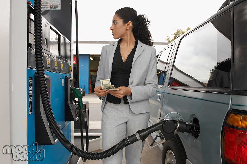 Woman standing by van with fuel pump counting money