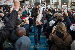 © Licensed to London News Pictures. 24/12/2018. London, UK. A customer carries a leg of pork away as butcher Harts of Smithfield auction off cuts of meat to the public on Christmas Eve at Smithfield Market in London. Photo credit: Rob Pinney/LNP