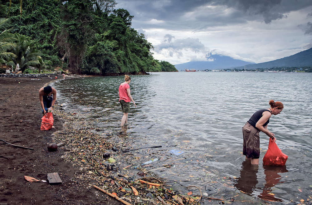 Tourists fill up rubbish bags with plastic trash and other debris on Lembeh Island, Sulawesi, Indonesia