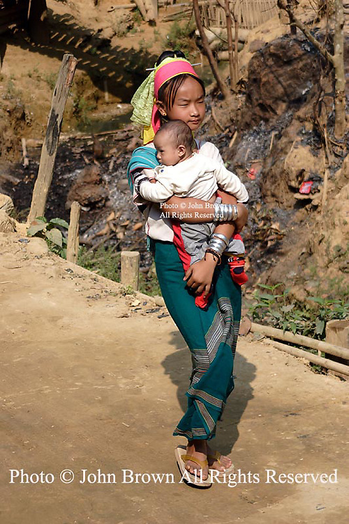 A Karen Paduang refugee woman from Burma (Myanmar) carries a young baby in the Ban Nai Soi refugee camp near Mae Hong Son, Thailand.  The ethnic Karen fled Burma to escape war atrocities and are considered a tourist attraction by Thailand's government.
