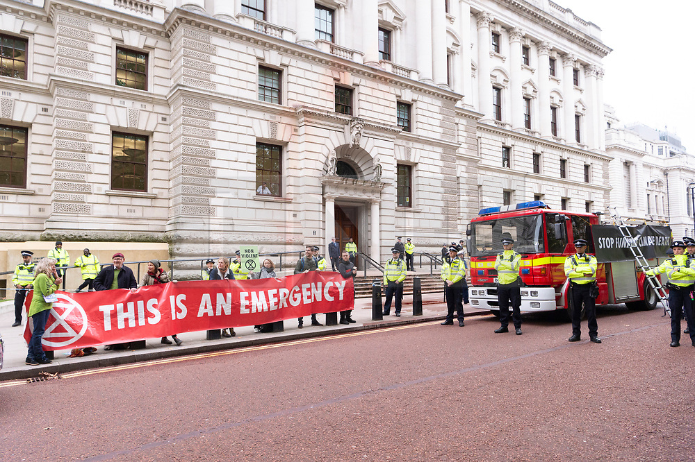"""© Licensed to London News Pictures. 03/10/2019. London, UK. Extinction Rebellion protesters stage a protest after using a fire engine to spray the front of the Treasury building with fake blood. Extinction Rebellion said it wanted to highlight the """"inconsistency between the UK Government's insistence that the UK is a world leader in tackling climate breakdown, while pouring vast sums of money into fossil exploration and carbon-intensive projects"""". Photo credit: Ray Tang/LNP"""