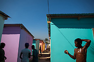 A teen bathes himself between new plywood homes in Camp Chaves in the Carrefour neighborhood of Port-au-Prince, Haiti, April 9, 2011. Residents were moved to this intentional camp along the waterfront after being evicted from the tent camp where they had taken refuge after last year's earthquake.  Their lease on this land expires in less than three years, at which time they will have to find new refuge.