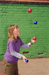 Young girl juggling balls,