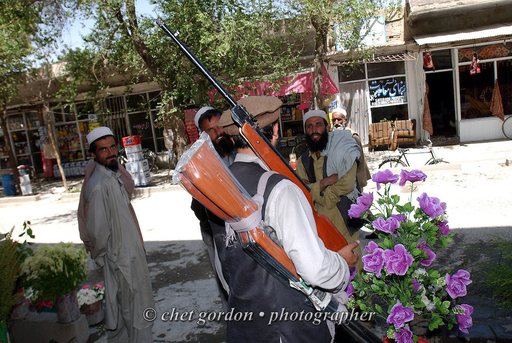 """A man sells rifles on the famed """"Chicken Street"""" in Kabul, Afghanistan on Monday, May 27, 2002."""