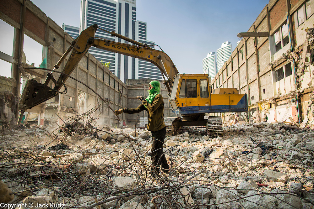 "11 DECEMBER 2012 - BANGKOK, THAILAND:  A worker recycles rebar while heavy equipment demolishes a building at ""Washington Square"" a notorious entertainment district off Sukhumvit Soi 22 in Bangkok. Demolition workers on many projects in Thailand live on their job site tearing down the building and recycling what can recycled as they do so until the site is no longer inhabitable. They sleep on the floors in the buildings or sometimes in tents, cooking on gas or charcoal stoves working from morning till dark. Sometimes families live and work together, other times just men. Washington Square was one of Bangkok's oldest red light districts. It was closed early 2012 and is being torn down to make way for redevelopment.    PHOTO BY JACK KURTZ"