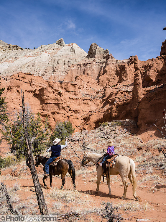 Family riders on horseback tour the Hat Shop in Kodachrome Basin State Park, Utah, USA. Geologists believe that ancient hot springs and geysers in the park area filled with sediment and solidified. Through time, the Entrada sandstone surrounding the solidified geysers eroded, leaving large sand pipes. 67 sand pipes rise in the park from 2 to 52 meters high. You can drive to the park from the north via a paved road from Cannonville and from the south via Cottonwood Canyon, Road 400, a dirt road from the Page, Arizona area, passable for most vehicles in dry conditions.