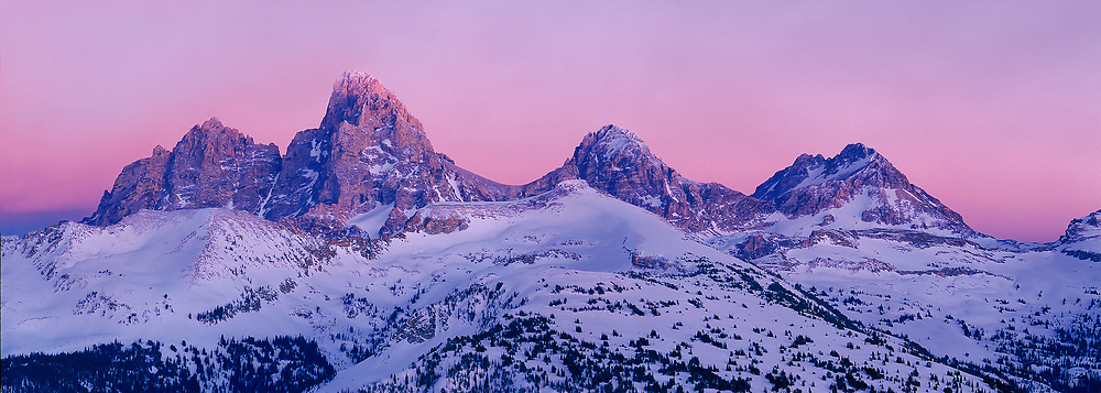 Alpine glow illuminates the snow covered peaks high in the Teton National Park.
