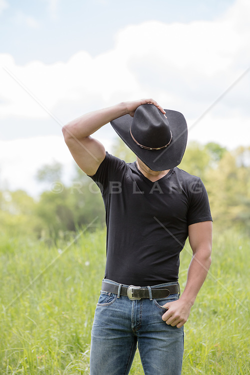 cowboy with hat covering his face outdoors