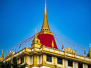 18 NOVEMBER 2015 - BANGKOK, THAILAND: The chedi of Wat Saket covered in red cloth at the start of the temple's annual fair. Wat Saket is on a man-made hill in the historic section of Bangkok. The temple has golden spire that is 260 feet high which was the highest point in Bangkok for more than 100 years. The temple construction began in the 1800s in the reign of King Rama III and was completed in the reign of King Rama IV. The annual temple fair is held on the 12th lunar month, for nine days around the November full moon. During the fair a red cloth (reminiscent of a monk's robe) is placed around the Golden Mount while the temple grounds hosts Thai traditional theatre, food stalls and traditional shows.      PHOTO BY JACK KURTZ