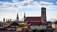 Münchens Skyline mit Blick auf den Alten Peter, die Frauenkirche, das neue Rathaus und die Alpen im Hintergrund.