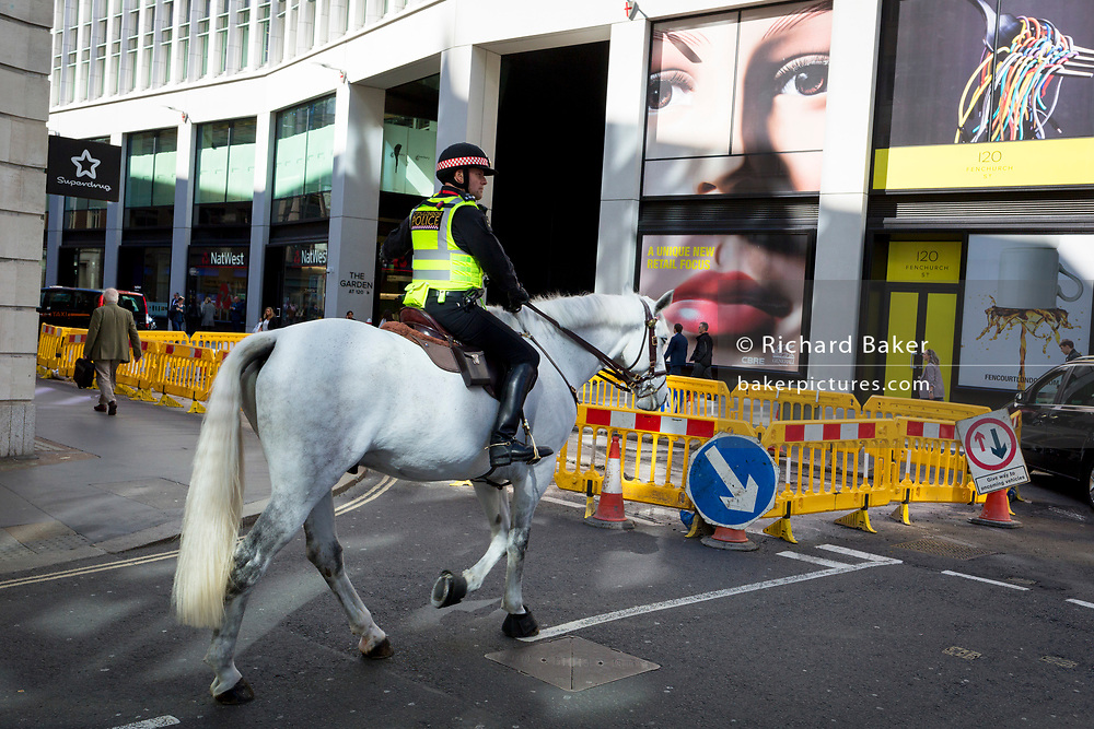 A pair of eyes and a mounted City police officer on Fenchurch Street - in the heart of the capital's financial district (aka The Square Mile),  on 25th September 2018, in London, England.