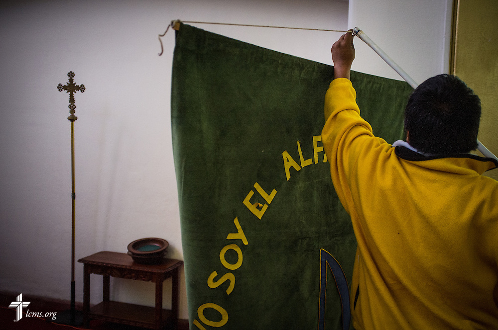 A man lifts a banner to hang on the wall before worship at the Lutheran Church of The Good Shepherd on Sunday, Jan. 15, 2017, in Mexico City. LCMS Communications/Erik M. Lunsford