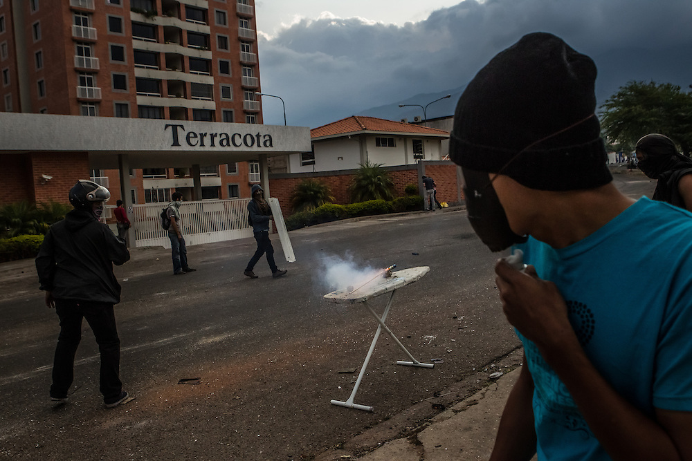 SAN CRISTOBAL, VENEZUELA: CREDIT: Youths clash with the national police, using an ironing board to launch a small rocket at the police. Anti-government protesters have taken to the streets, constructing barriers on nearly every block, completely gridlocking the city, to protest high inflation, high crime rates and shortages of basic goods, among other things. The protests in Venezuela began in San Cristobal, in the western state of Tachira, and are recognized as being the strongest in the country.  CREDIT:  Meridith Kohut for The New York Times
