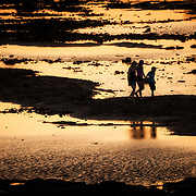 Three children silhouetted against the light of the setting sun on the waterfront of Panama City, Panama, on Panama Bay.