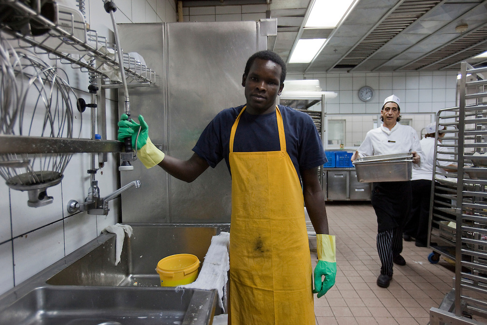 "A sudanese refugee  is washing dishes in the dairy kitchen  of the Royal Beach Hotel on February 28 2011. The municipality hung 1,500 red flags around the city as a sign of warning and put up hundreds of banners reading: ""Protecting our home, the residents of Eilat are drawing the line on infiltration."" Eilat Mayor Meir Yitzhak Halevi said that 10 percent of the city's population was currently made up of migrants and that the residents feel that the city has been conquered...Photo by Olivier Fitoussi."
