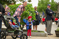"""Wearing their """"red, white and blue"""" this family watches as the parade rolls down Main Street towards Veteran's Square on Monday morning.  (Karen Bobotas/for the Laconia Daily Sun)"""