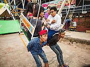 29 OCTOBER 2015 - YANGON, MYANMAR: Ride attendants hold onto a Ferris Wheel car during a street carnival in central Yangon. Electricity is scarce in Myanmar, especially in rural areas, and most traveling carnivals use human powered rides. Workers climb to the top of the Ferris Wheel and then pull it around getting it spinning. The carnival coincided with the Thadingyut Festival, the Lighting Festival of Myanmar, which is held on the full moon day of the Burmese Lunar month of Thadingyut, October or November on the Gregorian calendar. The carnival featured food, rides and games.      PHOTO BY JACK KURTZ