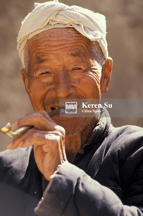 Portrait of a farmer smoking a pipe, Loess Plateau, Shaanxi Province, China