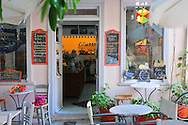 Cafe on Greek island of Syros with eclectic decor and colorful signs.