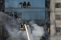 March 28, 2019 - Dhaka, Bangladesh - Bangladeshi firefighters work on ladders to fight a fire and rescue people. At least 19 people have been confirmed dead and scores more injured.  (Credit Image: © KM Asad/ZUMA Wire)